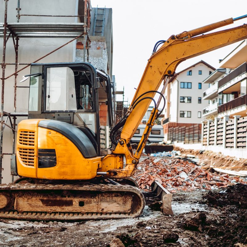 Yellow mini excavator digging fence foundation between construction site buildings